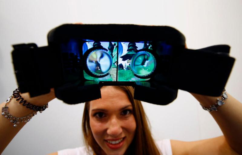 A woman shows VR goggles manufactured by hands-free 3D virtual reality system for smartphones Durivis during the Gamescom 2015 fair in Cologne